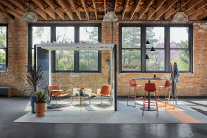 Break out collaborative spaces including an Orangebox Pod next to a bar height table near large exterior windows with natural light